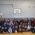 Foto di gruppo in palestra: nonni, alunni, docenti e dirigente scolastico