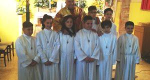 Il parroco e gli otto bambini che hanno ricevuto la Prima Comunione