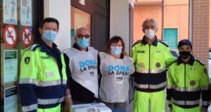 Volontari in azione all'ingresso della Coop