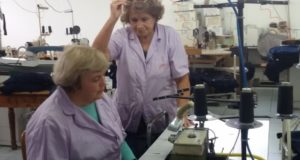 La signora Rita Frascarelli seduta al proprio tavolo di lavoro: al suo fianco la signora Lucia, fondatrice dell'azienda, passata a salutarla l'ultimo giorno di occupazione prima della meritata pensione