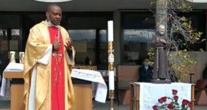 Il parroco durante la celebrazione pasquale; a destra la statua di Padre Pio