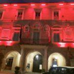 Il municipio illuminato di rosso
